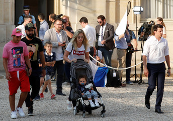Camille Tytgat, wife of France soccer player Rafael Varane, pushes their son Ruben as they arrive for a reception to honour the France soccer team after their victory in the 2018 Russia Soccer World Cup, at the Elysee Palace in Paris