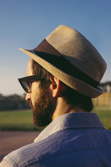 Rear view of man wearing sunglasses and hat while standing against clear blue sky during sunset