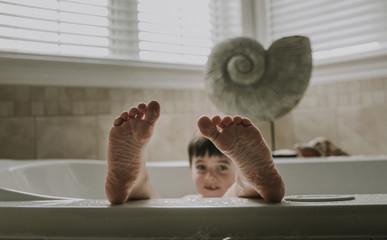 Portrait of boy taking bath in bathtub