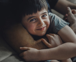Midsection of father embracing happy son while lying on sofa at home