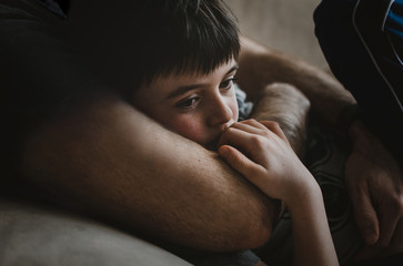 Midsection of father embracing thoughtful son while lying on sofa at home