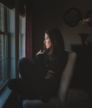 Thoughtful woman looking through window while sitting on chair at home
