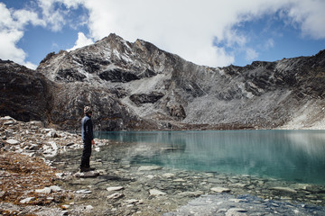 Side view of man standing at lakeshore against cloudy sky at Sagarmatha National Park