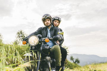 Portrait of couple sitting on motorcycle against sky