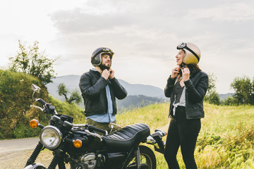 Couple wearing helmets while standing by motorcycle against sky