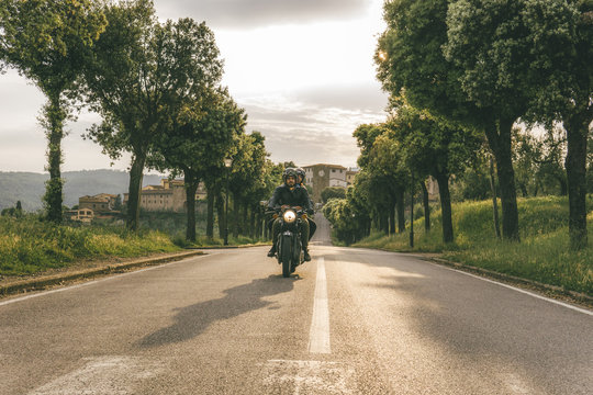 Couple riding motorcycle on road amidst trees