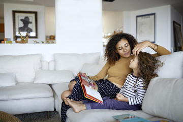 Mother reading picture book for daughter while sitting on sofa at home