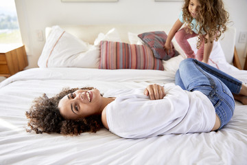 Portrait of happy mother playing with daughter while lying on bed at home