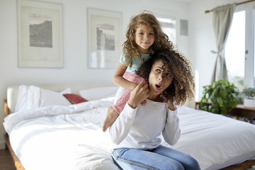 Daughter playing with mother sitting on bed at home