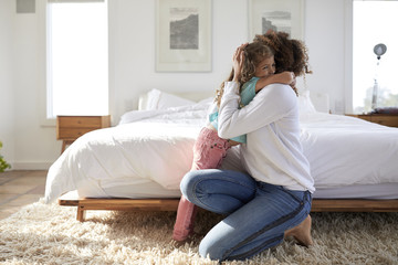 Side view of daughter embracing mother in bedroom at home