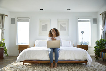 Happy woman using laptop computer while sitting on bed at home