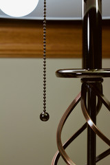 Abstract image of a modern metallic table lamp with pull chain