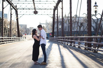 Side view of romantic couple looking at each other while standing on bridge against clear sky