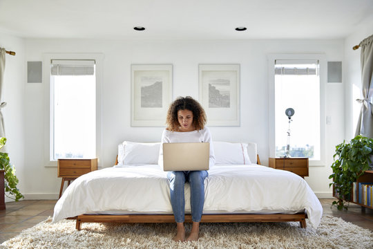 Woman using laptop computer while sitting on bed at home