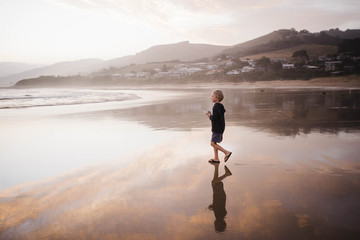 Boy looking walking at beach against sky during sunset