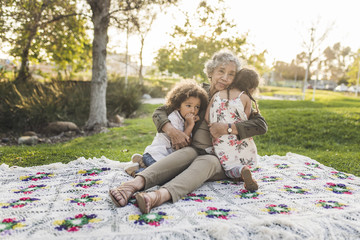Portrait of grandmother embracing grandchildren on picnic blanket at park