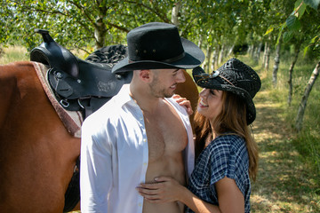 Handsome, beautiful Cowboy and cowgirl couple with horse and saddle on ranch holding and kissing on ranch