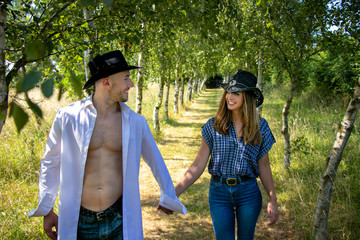 Cowboy and cowgirl couple with hats hold hands as they walk through avenue of trees on ranch