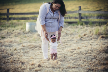 Mother assisting daughter in walking on grassy field at ranch