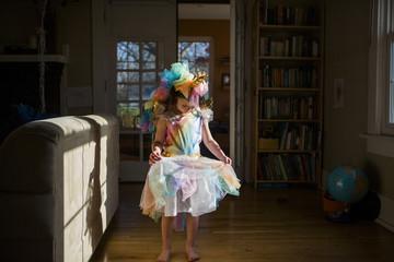 Full length of girl wearing colorful unicorn costume standing on hardwood floor at home