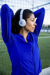 Thoughtful female athlete with arms raised listening music while standing by net