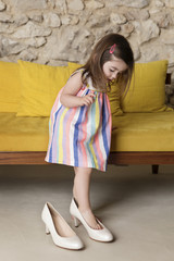 Girl wearing shoes while standing at home