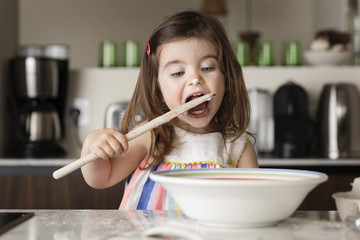 Girl tasting food while standing at kitchen