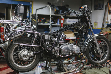 Close-up of old motorcycle in auto repair shop
