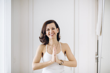 Portrait of smiling woman standing in prayer position at home