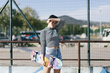 Portrait of woman holding skateboard while standing against fence during sunny day