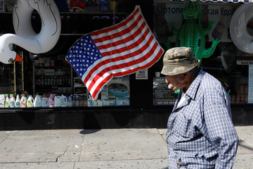 A man walks past a U.S. flag inflatable raft in the Brighton Beach section of Brooklyn, New York