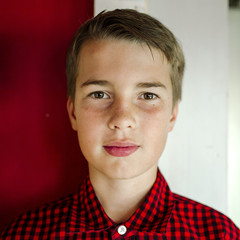 Close-up portrait of boy standing by wall at home