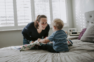 Happy mother talking with son playing on bed at home