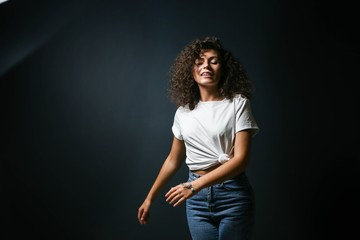 curly sexy beautiful woman is dancing and posing on a dark background. a brunette in fashionable clothes feels freedom and emancipation.