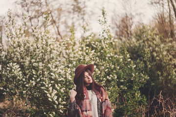 stylish hipster girl in hat and poncho with beautiful hair standing in park in evening sunshine. woman traveler in fashionable outfit relaxing in spring garden. space for text. atmospheric moment