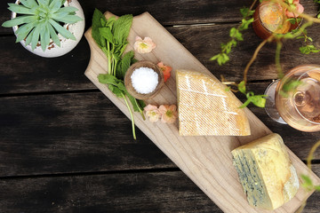 High angle view of cheese with wine and plants on wooden table