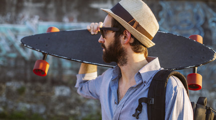 Man wearing hat while holding skateboard against wall