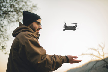 Side view of male hiker flying quadcopter while standing against clear sky during sunset
