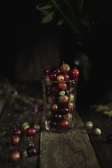 Food photo of a gooseberry in glass on a wooden old texture background. Photography in a dark low key. Macro shot.