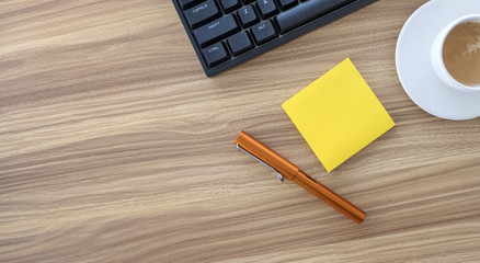 Wooden Desk with Keyboard Pen and Sticky Notes Shot Above