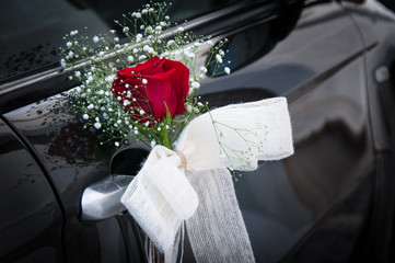 Ornament of red rose with white bow nicely decorates silver handle of black wedding car. Ceremony detail concept