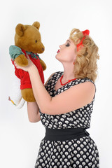 woman blonde in polka-dot dress with teddy bear in hands