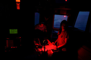 Head of mission Anabel Montes Mier of NGO Proactiva Open Arms rescue boat and crew member Esther Camps track the position of a rubber boat on a screen in central Mediterranean Sea