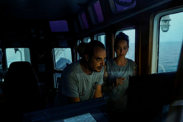 Marc Reig Creus captain of NGO Proactiva Open Arms rescue boat and the head of mission Anabel Montes Mier track the position of a rubber boat on a screen in central Mediterranean Sea