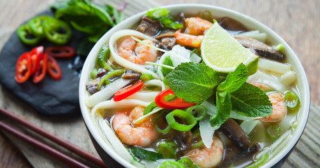 Vietnamese pho tom yum - Asian soup with king prawns rice noodles lime shiitake mushrooms fresh mint, chilli, spring, onions and sweet basil