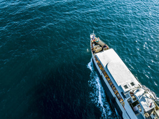 aerial top down view of travel ship nose part in the open sea