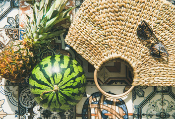Summer lifestyle background. Flat-lay of summer fruit pineapple and watermelon, straw bag and sunglasses over colorful moroccan tile floor, top view, close-up
