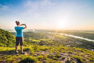 A Girl Standing on the Edge of the Cliff and Taking Photograph of the Sunset and the Valley with the River
