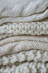 b687f233cb Background with warm sweaters. Pile of knitted clothes with autumn ...