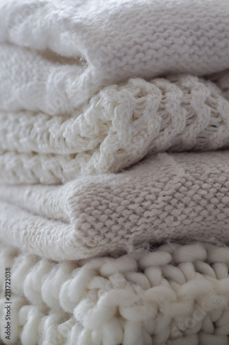 950fb9c7caaf Background with warm sweaters. Pile of knitted clothes in warm shades